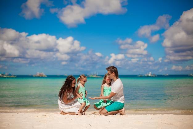 Giovane bella famiglia con due figlie divertirsi in spiaggia