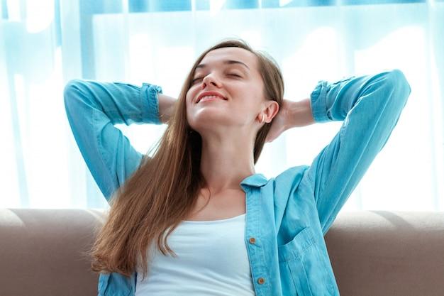 Giovane, bella, felice donna rilassante che riposa sul divano di casa dopo una lunga giornata di lavoro e godendo la solitudine