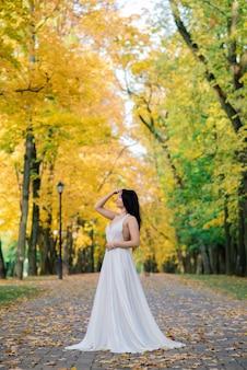 Giovane bella femmina castana in un vestito bianco lungo nel parco di autunno.
