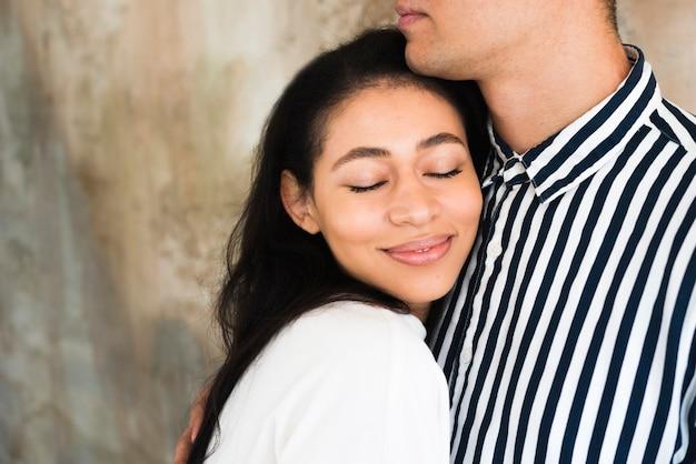 Giovane bella femmina sorridente che si appoggia sul ragazzo