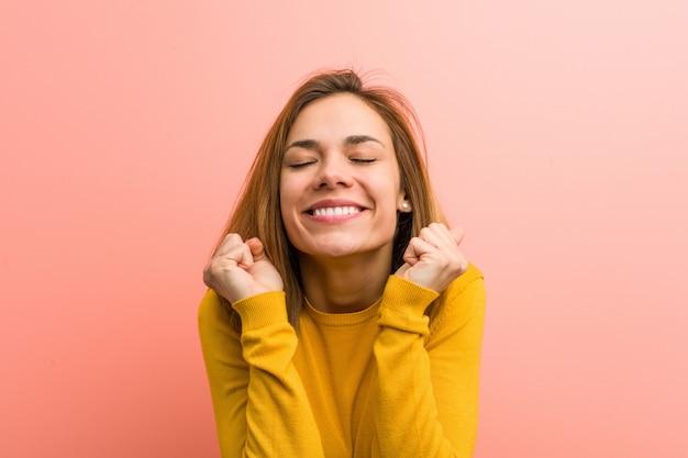 Giovane bella giovane donna alzando il pugno, sentirsi felici e di successo