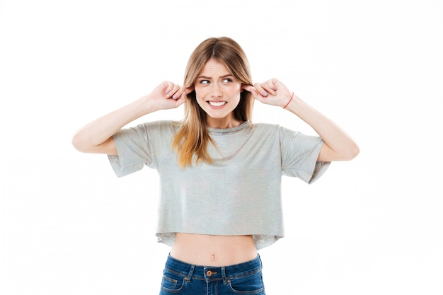 Giovane bella giovane donna bloccando le orecchie con irritazione
