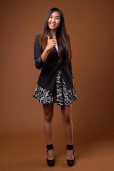 Giovane bella imprenditrice asiatica su sfondo marrone