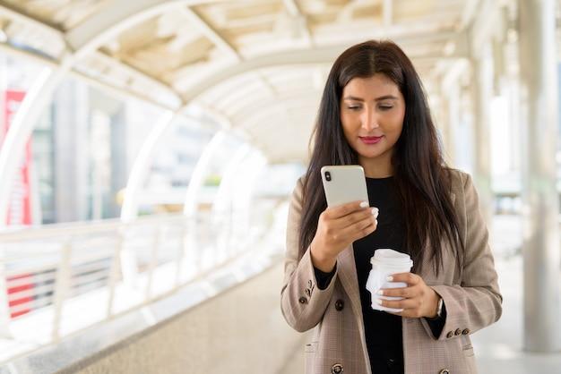 Giovane bella imprenditrice indiana utilizzando il telefono e un caffè in movimento in città