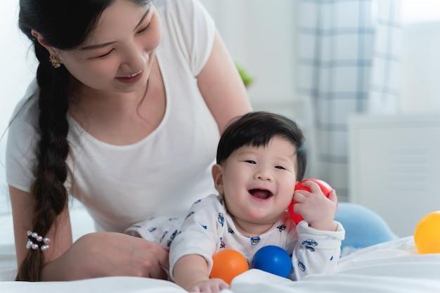 Giovane bella madre asiatica con il suo piccolo bambino sveglio sul letto.