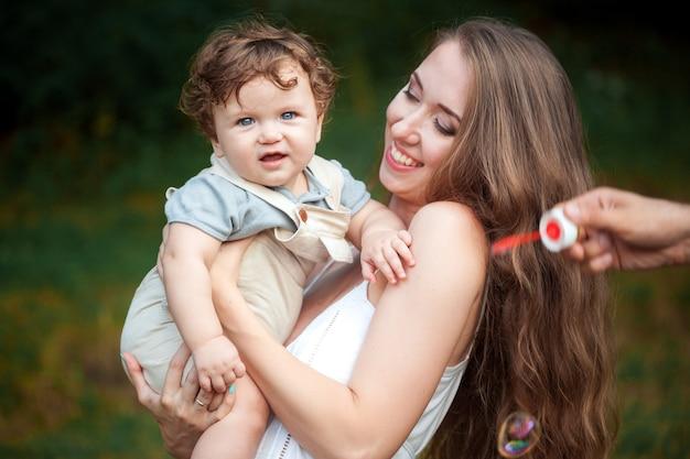 Giovane bella madre che abbraccia il suo piccolo figlio del bambino contro l'erba verde. donna felice con il suo bambino in una giornata di sole estivo. famiglia che cammina sul prato.