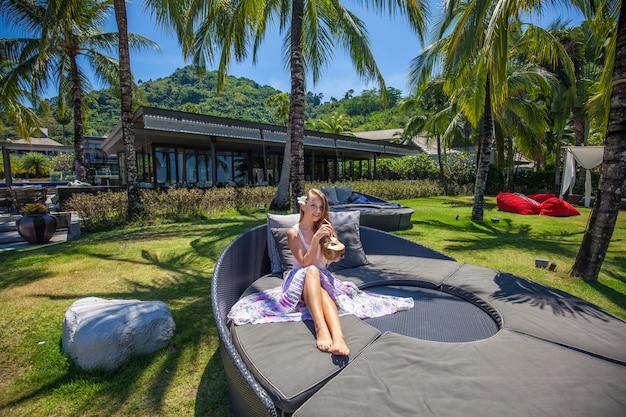 Giovane bella noce di cocco e rilassamento sorridenti della tenuta della donna