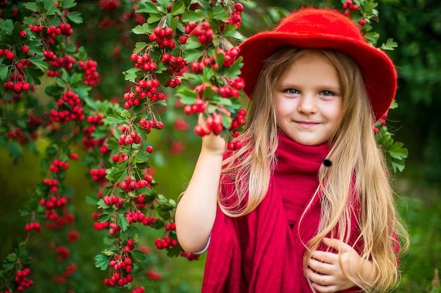 Giovane bella piccola ragazza alla moda in un parco soleggiato di autunno