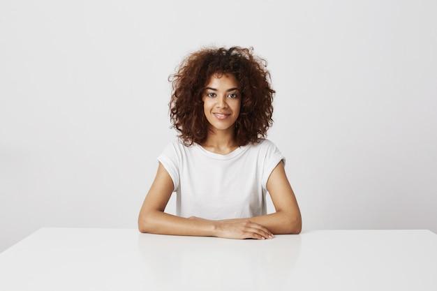 Giovane bella ragazza africana in seduta sorridente di vetro sopra la parete bianca