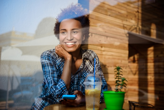 Giovane bella ragazza africana sorridente, tenendo il telefono, seduto nella caffetteria. sparato dall'esterno.