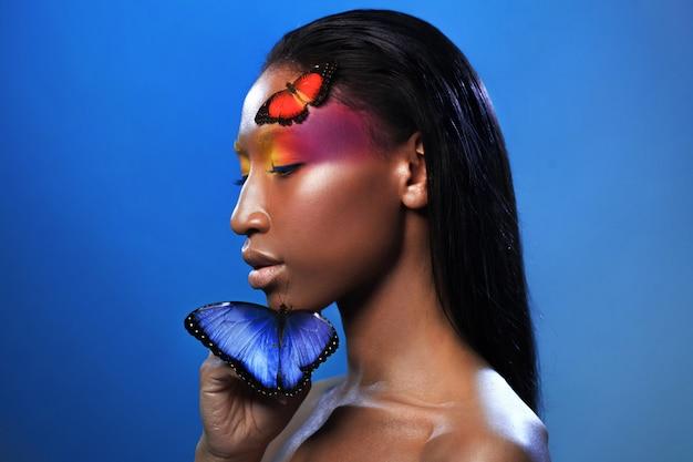 Giovane bella ragazza afro, con due farfalle, ritratto di bellezza