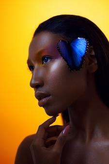 Giovane bella ragazza afro, con farfalla blu, ritratto di bellezza