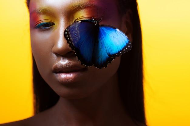 Giovane bella ragazza afro, vivida immagine con farfalla blu