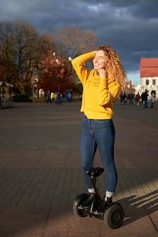 Giovane bella ragazza atletica in forma cavalcando hoverboard in strada