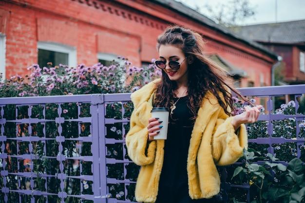 Giovane bella ragazza beve il caffè in un bicchiere per strada, ride e sorride