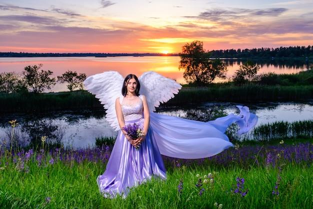 Giovane bella ragazza bianca con ali d'angelo e velo volante si trova su una collina con bouquet di fiori di campo viola nelle sue mani.