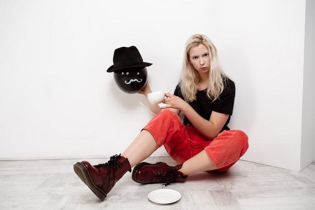 Giovane bella ragazza bionda che tiene baloon nero in cappello che si siede sul caffè bevente del pavimento sopra la parete bianca.