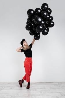 Giovane bella ragazza bionda che tiene baloons neri sopra la parete bianca.