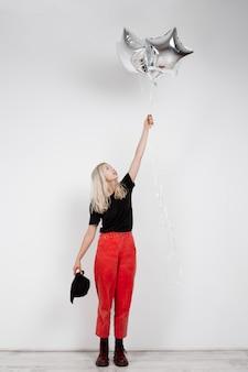 Giovane bella ragazza bionda che tiene i baloons d'argento sopra la parete bianca.