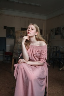 Giovane bella ragazza bionda in abito rosa puntellare la testa con il braccio.