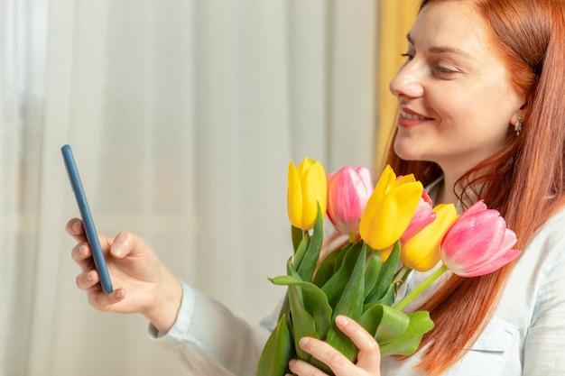 Giovane bella ragazza carina capelli lunghi che tiene un mazzo di tulipani freschi e prendendo selfie