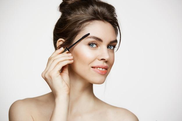 Giovane bella ragazza castana che sorride esaminando le sopracciglia della pittura della macchina fotografica con mascara sopra fondo bianco. beauty spa e cosmetologia.
