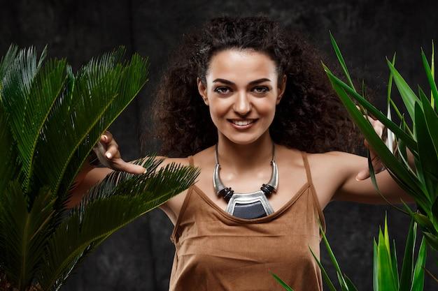 Giovane bella ragazza castana in piante tropicali sopra la parete grigia