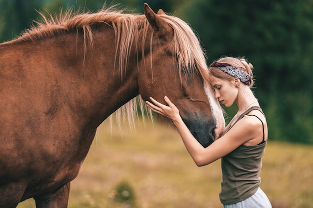Giovane bella ragazza che abbraccia cavallo alla natura