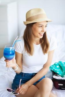 Giovane bella ragazza che beve un cocktail
