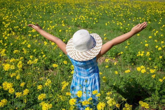Giovane bella ragazza che cammina e che balla attraverso un campo di papaveri, estate all'aperto