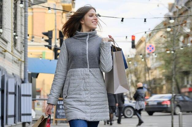 Giovane bella ragazza che cammina lungo la strada della città con i sacchetti della spesa