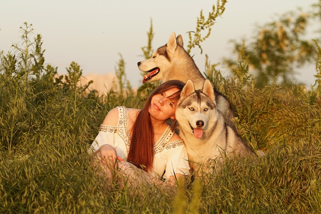 Giovane bella ragazza che gioca con un cane. giocando con il cane sul campo. husky siberiano.
