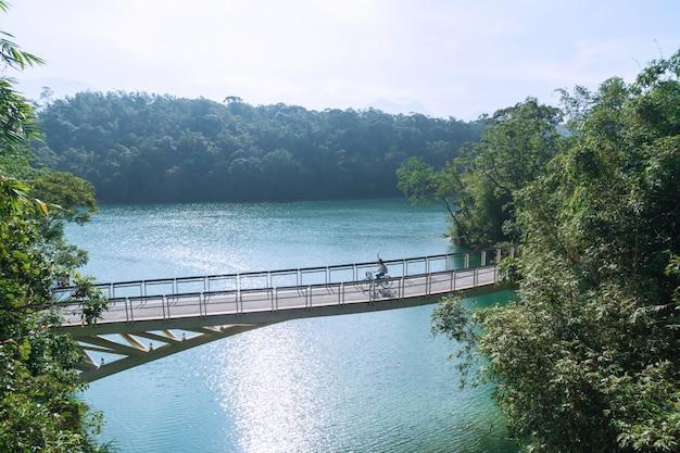 Giovane bella ragazza che guida una bicicletta sulla pista ciclabile nel lago di mattina. persone attive. all'aperto