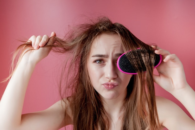 Giovane bella ragazza che ha problemi mentre capelli sulla parete rosa