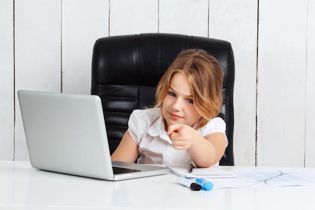 Giovane bella ragazza che indica dito la macchina fotografica in ufficio.