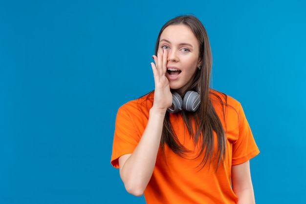 Giovane bella ragazza che indossa la maglietta arancione con le cuffie che dicono un segreto con la mano vicino alla bocca felice e positivo che sta sopra fondo blu isolato