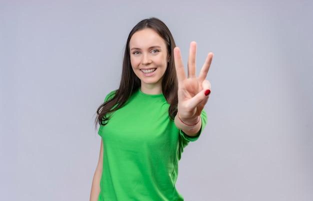 Giovane bella ragazza che indossa la maglietta verde che sorride allegramente mostrando e rivolto verso l'alto con le dita numero tre in piedi su sfondo bianco isolato