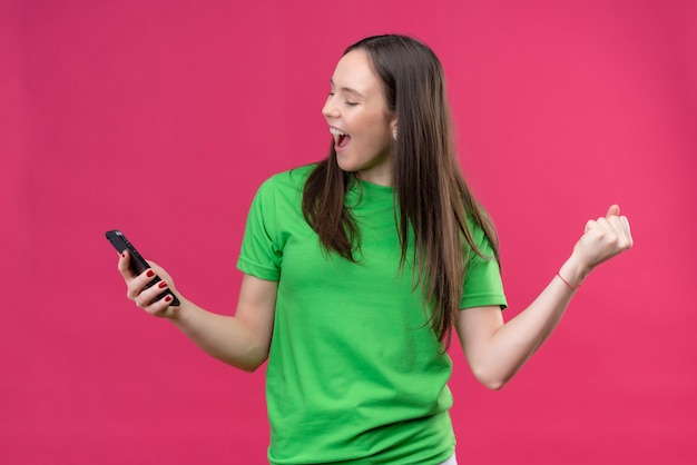 Giovane bella ragazza che indossa la maglietta verde che tiene smartphone uscito e felice alzando il pugno chiuso sorridendo allegramente gioendo il suo successo in piedi su sfondo rosa isolato