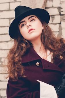 Giovane bella ragazza che indossa un cappello nero e cappotto