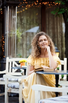 Giovane bella ragazza che legge, seduto nella caffetteria.