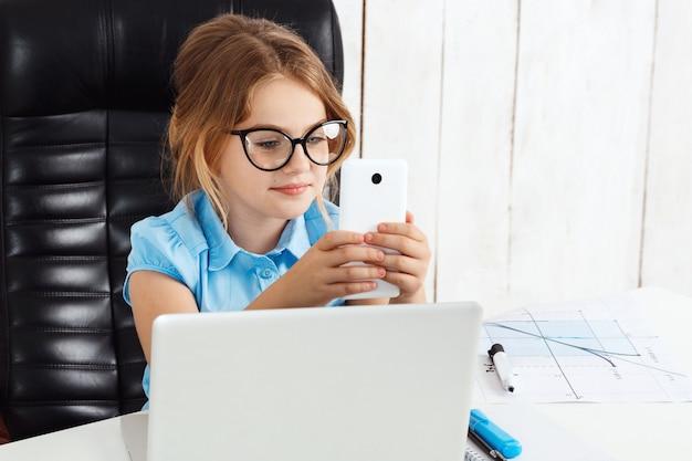 Giovane bella ragazza che osserva sul telefono il posto di lavoro.