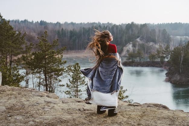 Giovane bella ragazza che posa su un lago