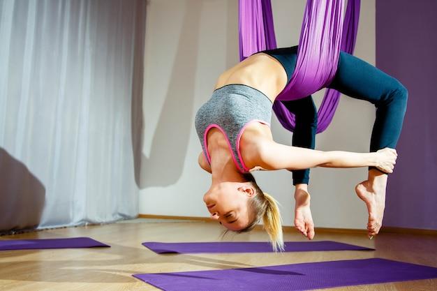 Giovane bella ragazza che pratica yoga aerea in palestra.