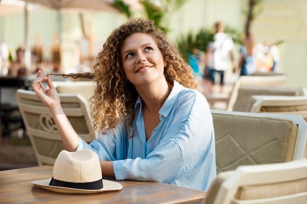 Giovane bella ragazza che si siede nella caffetteria.