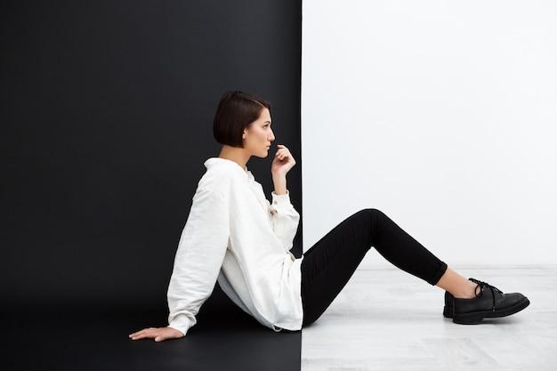 Giovane bella ragazza che si siede sul pavimento sopra la parete in bianco e nero