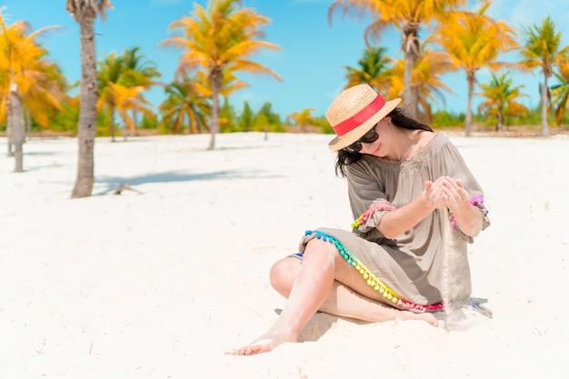 Giovane bella ragazza che si trova sulla spiaggia tropicale bianca come la neve