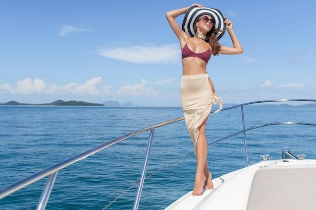 Giovane bella ragazza che sta sulla prua dell'yacht in un costume da bagno
