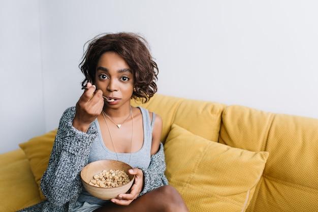 Giovane bella ragazza con i capelli ricci corti facendo colazione sana, mangiando muesli, muesli sul divano giallo, divano. atmosfera mattutina casalinga. indossare cardigan grigio, canottiera.