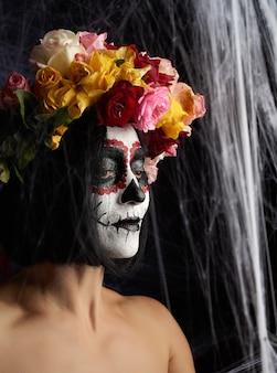 Giovane bella ragazza con la maschera di morte messicana tradizionale.