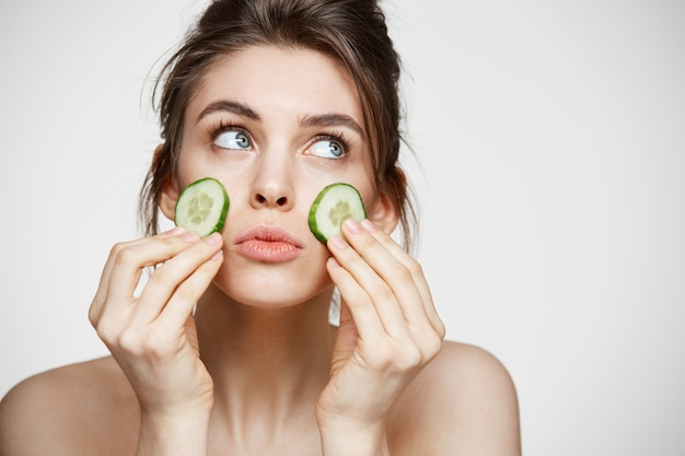 Giovane bella ragazza con le fette pulite perfette del cetriolo della tenuta della pelle sopra fondo bianco. cosmetologia e spa di bellezza.